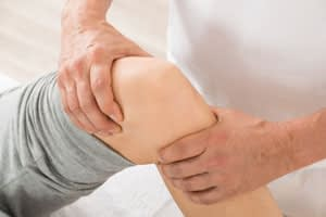 Physical Therapist examining a knee